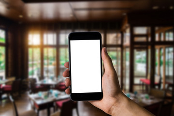 Hand holding white mobile phone with blank white screen  in cafe.