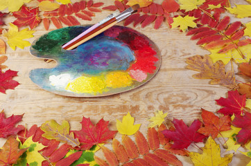 Art palette and brushes on wooden table framed in leaves