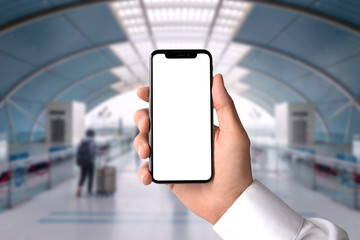 Centered, closeup of hand holding blank screen smartphone in train station terminal