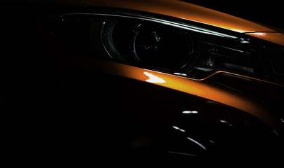 Closeup headlight of shiny orange luxury SUV compact car. Elegant electric car technology and business concept. Hybrid auto and automotive. Car parked in showroom or motor show. Car dealership.
