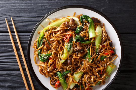 Chinese udon noodles with bok choy, shiitake and pepper close-up on a plate. Horizontal top view