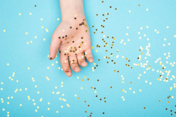 Gold glitter stars confetti on hands on a gentle pastel background. Universal festive background for your project. Horizontal, Copy space,
