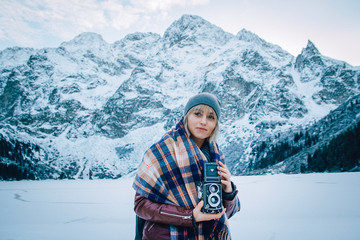 Beautiful girl makes a photo on an old vintage camera. In the mountains in winter, adventure and travel