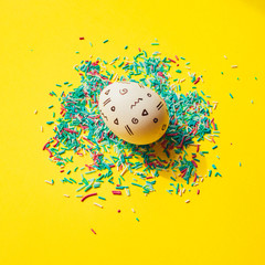 One Easter egg with memphis style print on yellow bright background with confetti.  Happy spring...