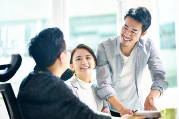 three happy asian teammates discussing business in office