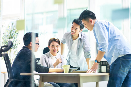 group of four asian teammates working together discussing business in office