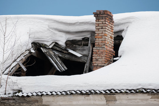 The roof collapsed under the weight of snow. Damaged falling roof and chimney on sunny day with clear blue sky.