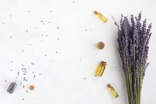 Organic cosmetic with lavender flowers and oil on white background with copy space, top view and flat lay