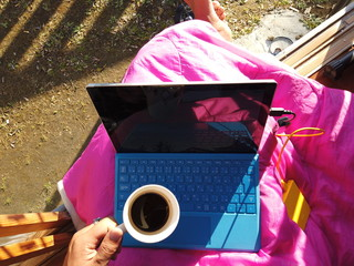 POV : man typing blue keyboard of note book and drinking coffee at home in winter in Japan.