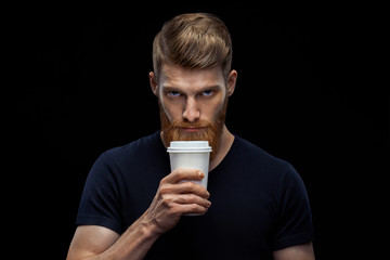 Studio shot of young caucasian bearded stylish man with cup of coffee