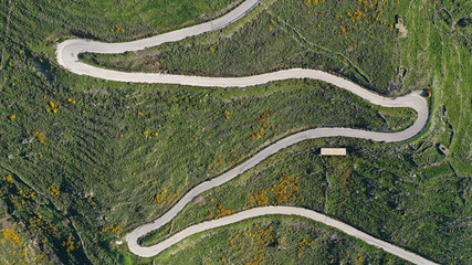 Aerial drone top view photo of serpentine snake curve road in green mountain with beautiful nature