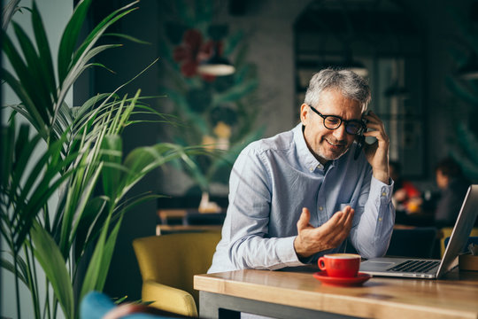 mature gray haired businessman talking on the smartphone in cafe bar
