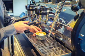 Barista making coffee latte art with espresso machine in cafe vintage color tone – man hand pouring cappuccino in large cup – closeup bartender serving coffee in coffee shop