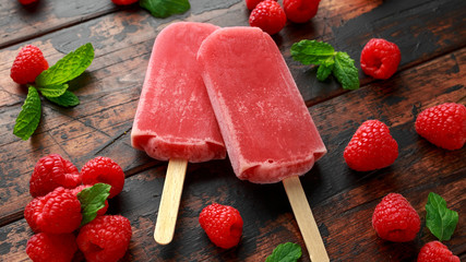 Homemade raspberry popsicles, ice lolly on wooden table. Summer food
