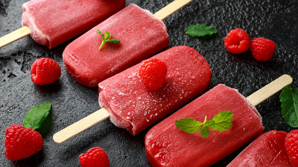 Homemade raspberry popsicles, ice lolly on rustic black background
