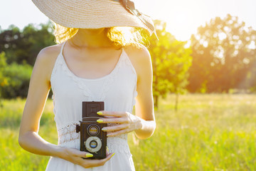 Happy beautiful fun girl woman hipster wear straw hat long white dress hold take picture old ancient rare photo camera on big large wide summer hot spring sunny green light field between fruit trees