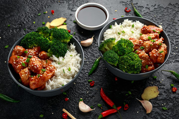 Teriyaki chicken, steamed broccoli and basmati rice served in two Asian clay bowls