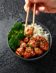 Teriyaki chicken, steamed broccoli and basmati rice served in bowl. person eating with chopsticks.