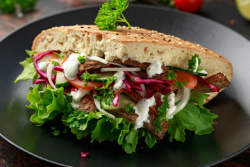 Doner kebab, fried lamb meat with vegetables and garlic sauce in turkish bread