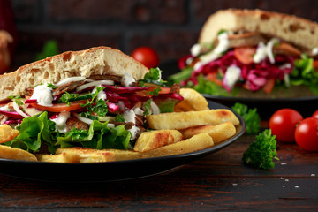 Doner kebab, fried lamb meat with vegetables, fries and garlic sauce in turkish bread