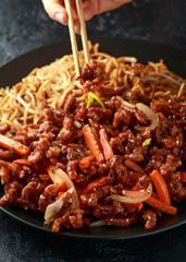 person eating egg noodles with bean sprouts, Crispy shredded beef, bamboo chopsticks