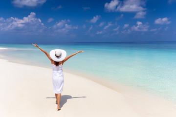 Attraktive, reisende Frau in weißem Sommerkleid läuft glücklich über einen tropischen Strand mit türkisem Meer und feinem Sand