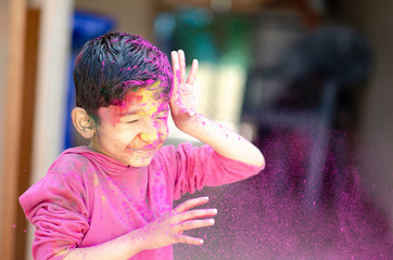Cute Little Indian boy child with coloured face paint poweder color thrown at his face during holi indian festival looking at camera