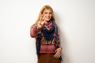 Hippie woman over white wall happy and counting three with fingers