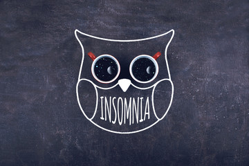Insomnia, sleeplessness, sleeps disorder, trouble sleeping, mental exercise concept. Two cups of coffee in owl contour and word insomnia on the star night background