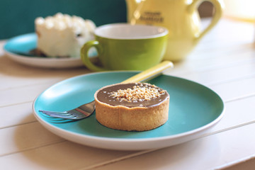 Salted caramel round cake on blue plate with fork, yellow tea pot and green cup. Delicious caramel chocolate tart, topped with nuts