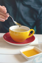 Mans hand with a spoon of honey over a yellow cup of tea. Tea time in cafe, Tea party