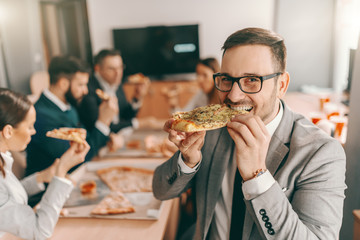 Young unshaven businessman in formal wear and eyeglasses eating pizza for lunch. In background colleagues also eating lunch. Together we stand, divided we fall.