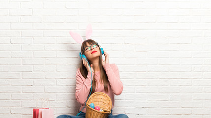 Woman with bunny ears for Easter holidays sitting on the floor listening to music with headphones