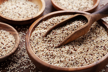 Quinoa in bowl on wooden kitchen table. Healthy and diet superfood product.
