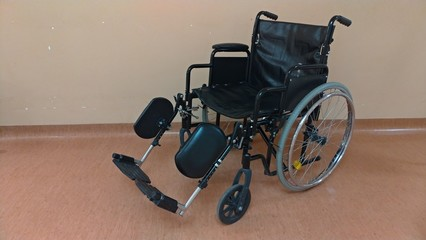 Disabled carriage. Black wheelchair in the hospital for the transportation of seriously ill people