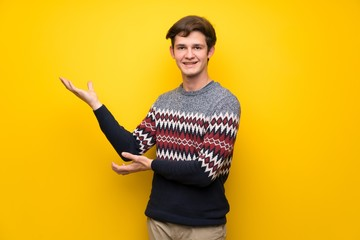 Teenager man over yellow wall extending hands to the side for inviting to come