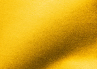 Gold paper texture background metallic golden foil or shiny wrapping bright yellow wallpaper sheet for design decoration element