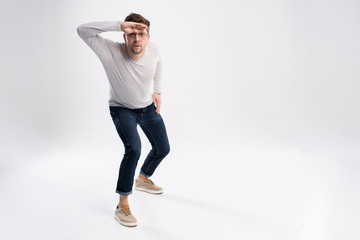 Funny man in casual is having some fun. He is posing and dancing. Isolated on white background.