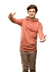 Teenager man with sweatshirt presenting and inviting to come with hand over isolated white background