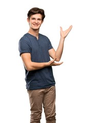Teenager man extending hands to the side for inviting to come over isolated white background