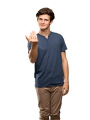 Teenager man inviting to come with hand. Happy that you came over isolated white background