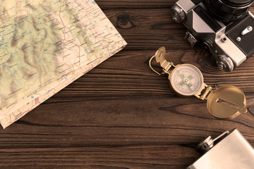 Geographical map, retro camera, compass on a wooden background. travel, tourism, recreation
