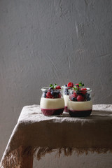 Homemade classic dessert Panna cotta with raspberry and blueberry berries and jelly in jars, decorated by mint leaves over linen table cloth with grey wall at background.