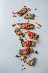 Homemade energy oats granola bars with dried fruits and nuts whole and broken wrapped in red paper over white texture background. Healthy snack. Flat lay, space