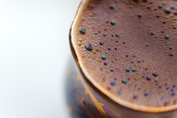 ISOLATED: Macro shot of brewed coffee in a round cup - Rainbow sparkles with bubbles