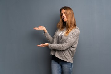 Blonde woman over grey background extending hands to the side for inviting to come