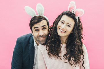 Young family on pink background. Easter Happy couple. Holiday. A tiny ear. People from the rabbit ears. Get rid of stupid. A man makes a rabbit expression alone.
