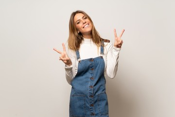 Beautiful woman over isolated white wall smiling and showing victory sign with both hands