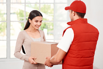 Treat Your Customers Right. Young woman receiving parcel from delivery man