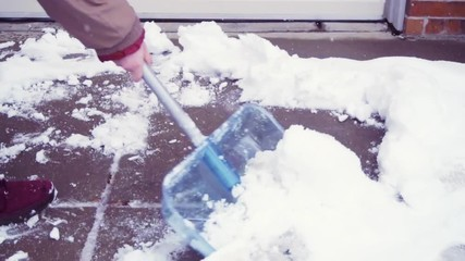 Wall Mural - Slow motion. Young man shoveling snow from driveway.